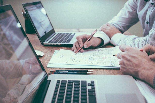 To mennesker sidder ved et skrivebord ved deres computere og arbejder med SEO