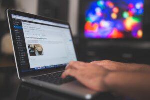 En person sidder ved sin bærbare pc med hænderne ved tastaturet, i gang med at skrive en fængende overskrift