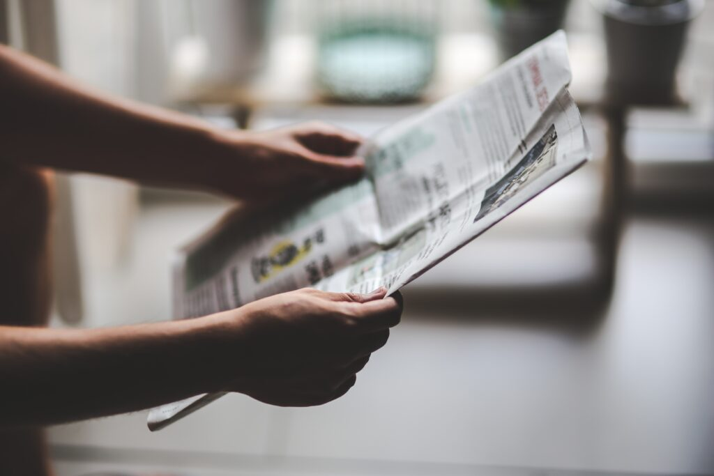 En person holder en avis i strakte arme og læser alle de gode overskrifter