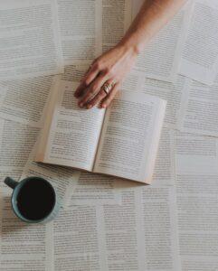Uendelige sætninger med bog placeret ovenpå en masse stykker papir