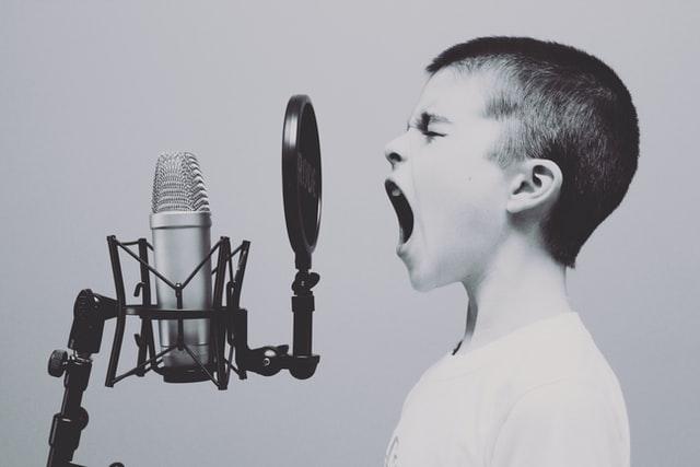 Lille dreng synger i mikrofon, hans egen eksterne kommunikation til omverden