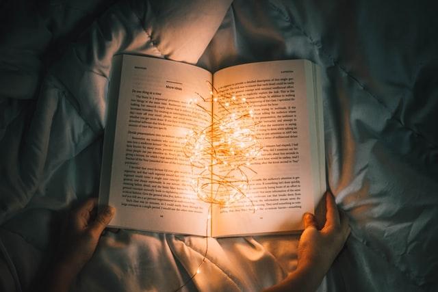 En person læser en bog i sengen med en lyskæde som skaber stemning, for at illustrere hvad en tone of voice kan betyde for læsningen