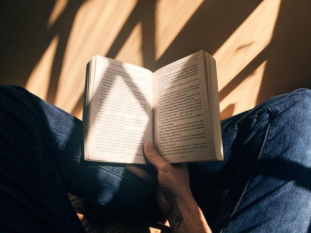 Forfatterspire sidder på gulvet med benene over kors og læser en bog
