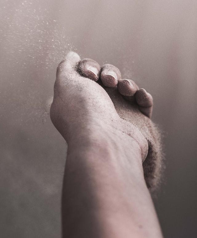 En hånd hvor sand løber gennem fingrene i et flygtigt øjeblik
