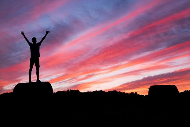 En mand står med armene strakt over hovedet på toppen med solnedgangen i baggrunden