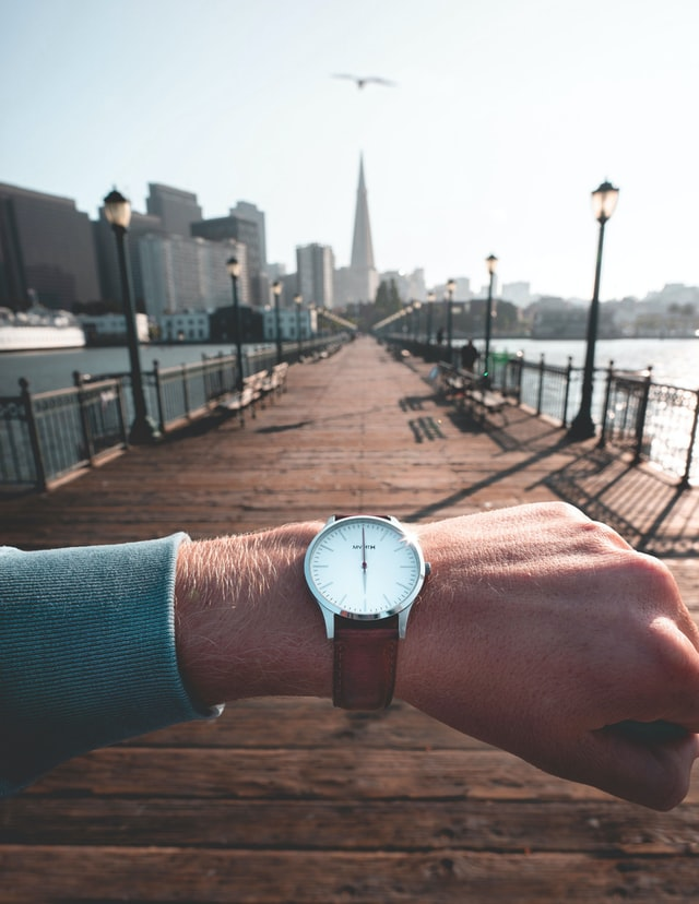 En subjektiveret mand tjekker tiden på sit armbåndsur, på en bro med byen i baggrunden