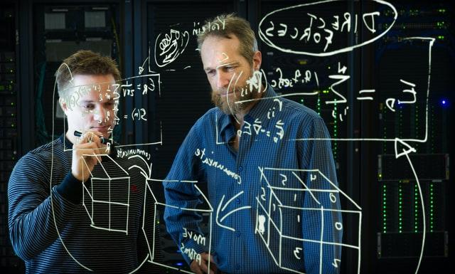 To mænd står og prøver at få overblik over de grammatiske regler, det kan være et større regnestykke
