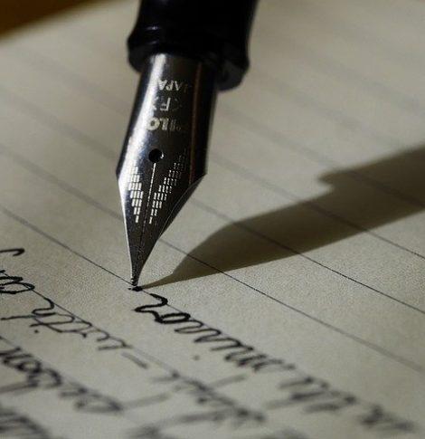 En fyldepen noterer skrivetips på et papir med stiplede linjer